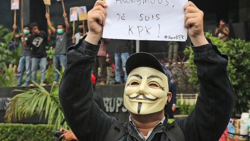 "A masked supporter of Indonesian Corruption Eradication Commission (KPK) holds up a poster that reads ""I am KPK"" during a protest against the arrest of the deputy head of the Corruption Eradication Commission Bambang Widjojanto by the police, outside the commission's office in Jakarta, Indonesia, Friday, Jan. 23, 2015. Widjojanto was arrested Friday, days after he said a national police chief hopeful was a graft suspect, sparking public demands for the country's president to defend the body. (AP Photo/tatan Syuflana)"