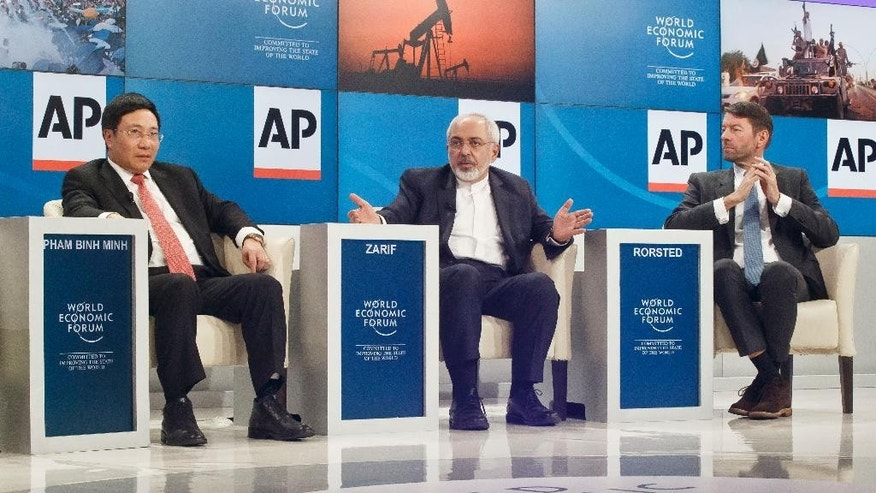 "Iranian Foreign Minister Mohammad Javad Zarif, center, gestures as he speaks during a panel discussion entitled ""The  Geopolitical Outlook"", flanked by Foreign Minister of Vietnam Pham Binh Minh, left, and CEO of Henkel AG Kasper Rorsted of Denmark at the World Economic Forum, Friday, Jan. 23, 2015. The world's financial and political elite will head this week to the Swiss Alps for 2015's gathering of the World Economic Forum at the Swiss ski resort of Davos. (AP Photo/Michel Euler)"