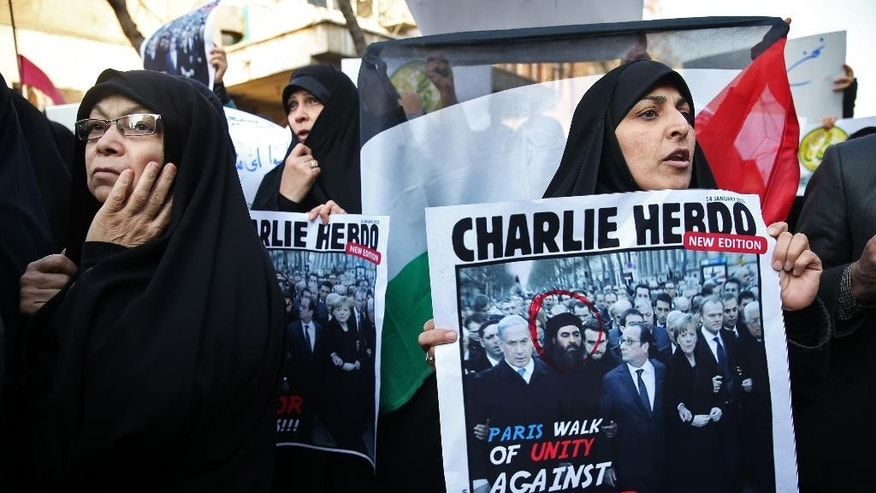 An Iranian demonstrator holds a satirical poster cover mocking the French weekly Charlie Hebdo which shows the Paris rally but adds a portrait of the Islamic State group's leader and self-proclaimed caliph Abu Bakr al-Baghdadi among the world leaders, during a protest in front of the French Embassy in Tehran, Iran, Monday, Jan. 19, 2015. (AP Photo/Ebrahim Noroozi)