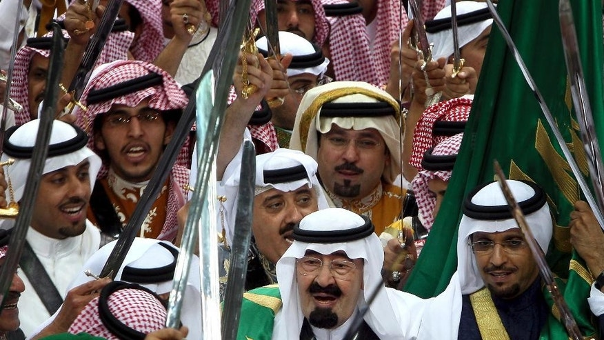 FILE - In this March 23, 2010 file photo, King Abdullah, center, of Saudi Arabia surround by Saudi top princes holds his sword as he takes part in the traditional Arda dance, or War dance, during the Janadriyah Festival of Heritage and Culture on the outskirts of Riyadh. On early Friday, Jan. 23, 2015, Saudi state TV reported King Abdullah died at the age of 90.  (AP Photo, File)