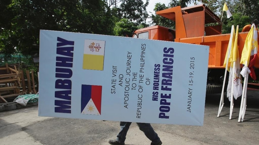 In this Tuesday Jan. 20 photo, a Filipino worker carries a tarpaulin greeting Pope Francis as they take off signs and flags at the venue where he held his holy mass in Manila, Philippines. When the pope comes to town, a huge bill awaits the host country, but for many, mammoth crowds whipped up by the Roman Catholic Church leader offer plenty of good business. (AP Photo/Aaron Favila)
