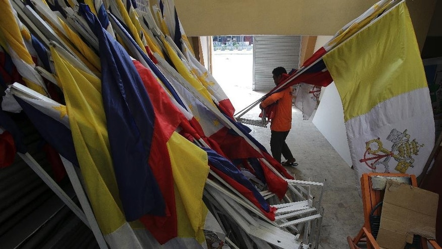 In this Tuesday Jan. 20 photo, a Filipino worker carries the Vatican and Philippine flag inside a store room, the same area where Pope Francis held a holy mass in Manila, Philippines. When the pope comes to town, a huge bill awaits the host country, but for many, mammoth crowds whipped up by the Roman Catholic Church leader offer plenty of good business. (AP Photo/Aaron Favila)