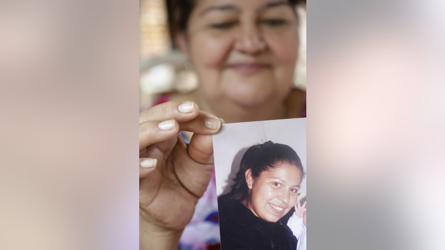 In this Jan. 16, 2015 photo, Arminda Escobar de Amarilla holds a 2011' family's book picture of her daughter Rosalia Amarilla, in Nemby, Paraguay. Paraguayan Rosalia Amarila was detained for drugs trafficking in Beijing airport in July 24, 2012, and faces a death sentence. (AP Photo/Jorge Saenz)