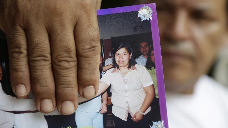 In this  Jan. 16, 2015 photo, Jose Amarilla holds a 2011' family's book picture of his daughter Rosalia Amarilla, in Nemby, Paraguay. Paraguayan Rosalia Amarila was detained for drugs trafficking in Beijing airport in July 24, 2012, and faces a death sentence. (AP Photo/Jorge Saenz)