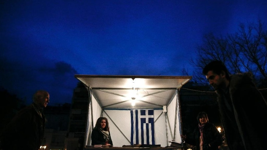 A Greek flag is seen inside a kiosk of the New Democracy party, as people walk by in Athens on Tuesday, Jan. 20, 2015. Weekend opinion polls showed conservative Prime Minister Antonis Samaras' New Democracy party trailing the anti-bailout Syriza party in voter support and that a coalition government is likely to emerge from Sunday's vote. (AP Photo/Petros Giannakouris)