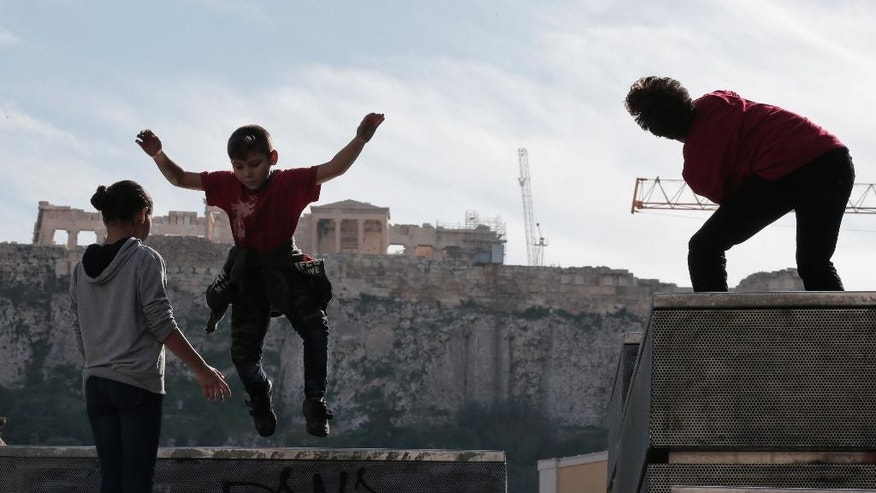 Backdropped by the Parthenon on Acropolis hill, children, left, play as a street dancer, right, performs, in central Athens, Tuesday, Jan. 20, 2015. Greek Prime Minister Antonis Samaras' conservative New Democracy party has failed so far to overcome a gap in opinion polls with the anti-bailout Syriza party ahead of the Jan. 25 general election. Weekend opinion polls showed New Democracy party trailing the anti-bailout Syriza party in voter support and that a coalition government is likely to emerge from Sunday's vote. (AP Photo/Lefteris Pitarakis)