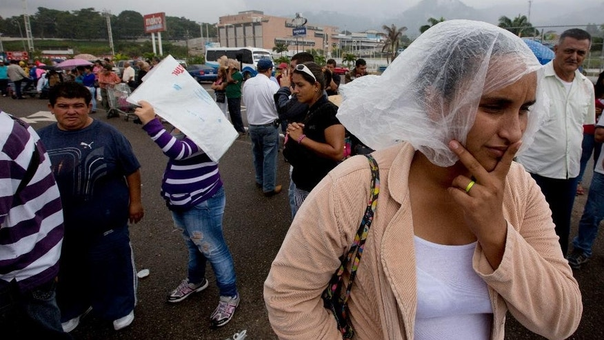 A woman waits in a line in a light rain, hoping to find soap and toilet paper at a supermarket to purchase, in San Cristobal, Venezuela, Thursday, Jan. 22, 2015. Venezuela's crisis has only deepened with falling crude prices crippling the oil-dependent economy, leading to a cash crunch that has restricted imported goods to just a trickle. Basic items like flour and diapers are hard to come by even on the black market and the government has had to deploy soldiers to keep peace outside stores where people wait hours for a chance to pick through near-barren shelves. (AP Photo/Fernando Llano)