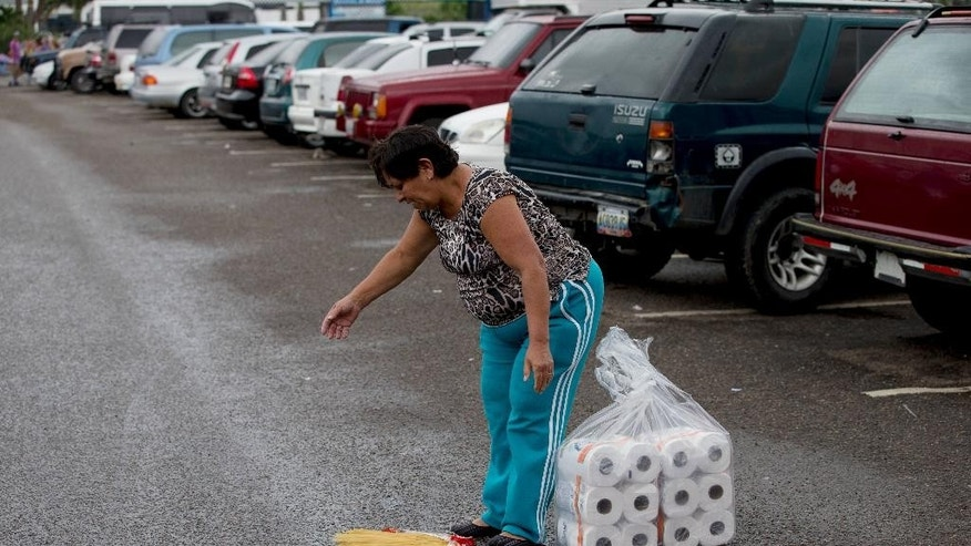 A woman stops to pick up a package of discarded pasta in a supermarket parking lot after purchasing toilet paper at a regulated price, in San Cristobal, Venezuela, Thursday, Jan. 22, 2015. Basic items like flour and diapers are hard to come by even on the black market and the government has had to deploy soldiers to keep peace outside stores where people wait hours for a chance to pick through near-barren shelves. (AP Photo/Fernando Llano)