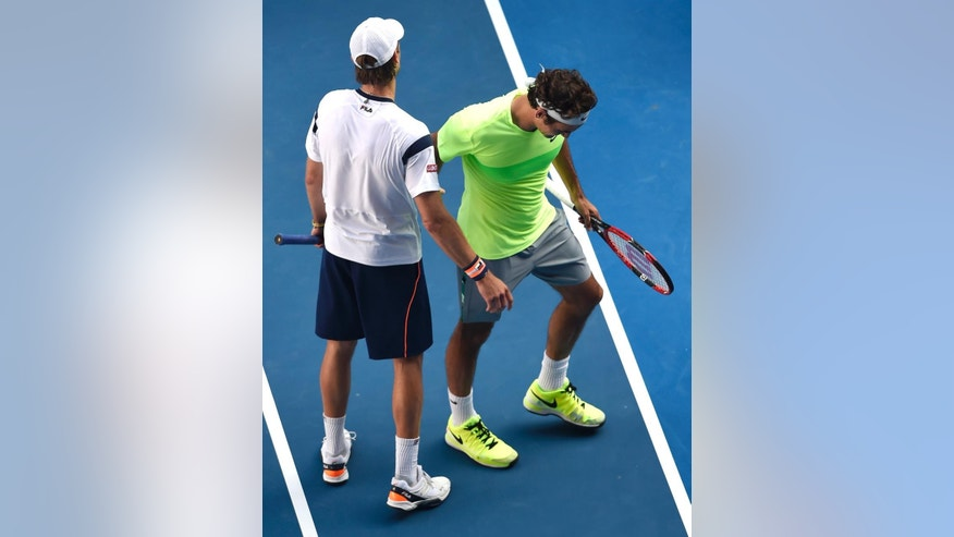 Roger Federer of Switzerland, right, and Andreas Seppi of Italy on the court after Federer's  third round loss to Seppi at the Australian Open tennis championship in Melbourne, Australia, Friday, Jan. 23, 2015. (AP Photo/Andy Brownbill)