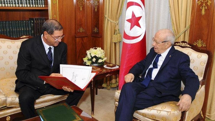 New Tunisian Prime Minister Habib Essid, left, and Tunisian President Beji Caid Essebsi check the list of the cabinet members, Friday, Jan.23, 2015 in Tunis. A month after the last election ending its democratic transition, Tunisia announces the makeup of the new coalition government tasked with seeing the country out of its current economic crisis. (AP Photo/Hassene Dridi)