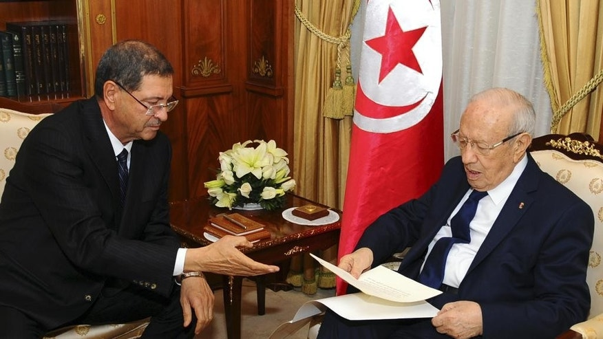 New Tunisian Prime Minister Habib Essid, left, gives Tunisian President Beji Caid Essebsi the list of the cabinet members, Friday, Jan.23, 2015 in Tunis. A month after the last election ending its democratic transition, Tunisia announces the makeup of the new coalition government tasked with seeing the country out of its current economic crisis. (AP Photo/Hassene Dridi)