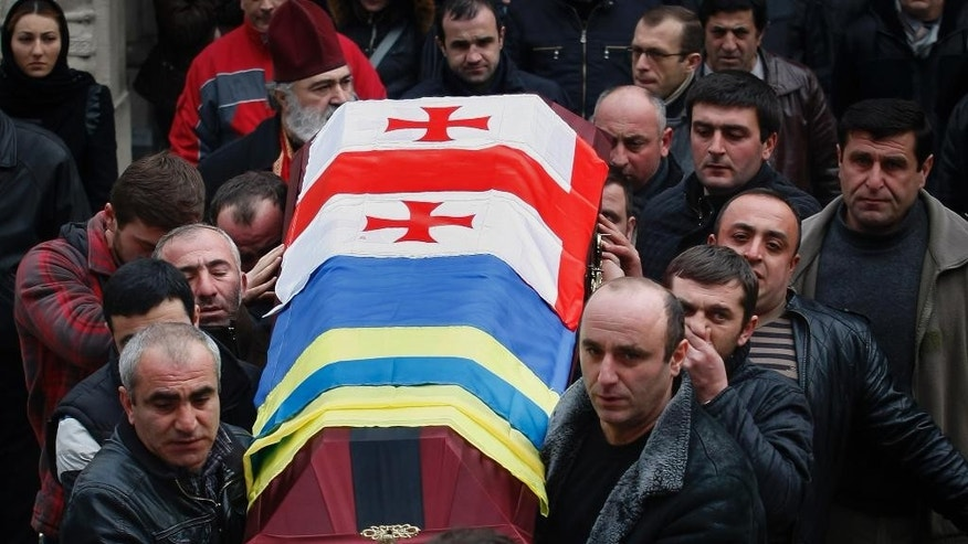 CORRECT SPELLING OF FIRST NAME TO TAMAZ  Georgian men carry a casket with the body of Tamaz Sukhiashvili, a Georgian national who was killed in fighting against Russian-backed separatists in eastern Ukraine, during a funeral ceremony in Tbilisi, Georgia, Thursday, Jan. 22, 2015. (AP Photo/Shakh Aivazov)