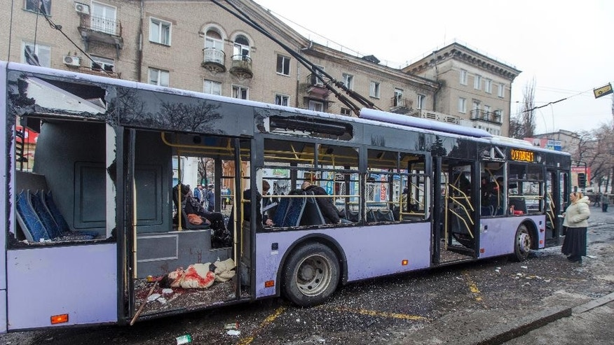 Passengers killed when a trolley bus was damaged by a mortar shell are seen inside a bus in Donetsk, eastern Ukraine, Thursday, Jan. 22, 2015. A new peace initiative for Ukraine began taking shape as mortar shells rained down Thursday on the center of the main rebel-held city in the east, killing at least 13 people at a bus stop. The civilian death toll has been mounting steadily in the conflict between Ukrainian troops and Russian-backed separatists that the United Nations says has killed more than 4,700 people since April. (AP Photo/Igor Ivanov)