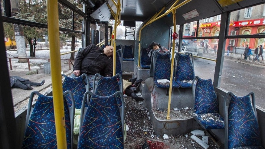 Passengers killed when a trolley bus was damaged by a mortar shell are seen in interior of the bus  and outside, left, in Donetsk, eastern Ukraine, Thursday, Jan. 22, 2015. A new peace initiative for Ukraine began taking shape as mortar shells rained down Thursday on the center of the main rebel-held city in the east, killing at least 13 people at a bus stop. The civilian death toll has been mounting steadily in the conflict between Ukrainian troops and Russian-backed separatists that the United Nations says has killed more than 4,700 people since April. (AP Photo/Igor Ivanov)