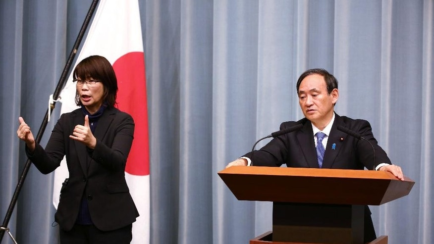 "Japan's Government spokesman Chief Cabinet Secretary Yoshihide Suga, right, accompanied by a sign language interpreter answers questions during a press conference at the prime minister's office in Tokyo Sunday, Jan. 25, 2015. Prime Minister Shinzo Abe said Sunday he was ""speechless"" after an online video purportedly showed that one of two Japanese hostages of the extremist Islamic State group had been killed, and he demanded the release of the other. (AP Photo/Eugene Hoshiko)"
