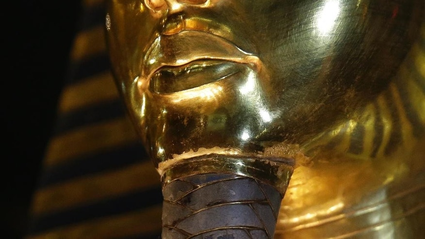 A detail of the gold mask of King Tutankhamun showing where the beard is attached is seen in a glass case during a press tour, in the Egyptian Museum near Tahrir Square, Cairo, Egypt, Saturday, Jan. 24, 2015. German restoration specialist, Christian Eckmann, summoned to Cairo to examine the damaged burial mask, spoke at a packed news conference Saturday at the Egyptian museum, saying that epoxy used to glue the mask's beard back on can be removed and the mask properly restored. Eckmann said the beard, which has been detached before from the mask and had likely loosened over the years, was accidentally knocked off last August during work on the relic's lighting. (AP Photo/Hassan Ammar)