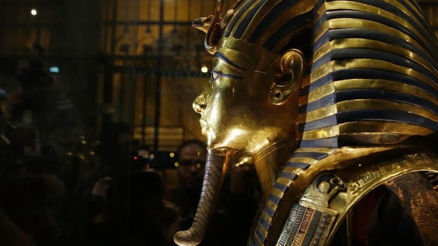 The gold mask of King Tutankhamun is seen in a glass case during a press tour, in the Egyptian Museum near Tahrir Square, Cairo, Egypt, Saturday, Jan. 24, 2015. German restoration specialist, Christian Eckmann, summoned to Cairo to examine the damaged burial mask, spoke at a packed news conference Saturday at the Egyptian museum, saying that epoxy used to glue the mask's beard back on can be removed and the mask properly restored. Eckmann said the beard, which has been detached before from the mask and had likely loosened over the years, was accidentally knocked off last August during work on the relic's lighting. (AP Photo/Hassan Ammar)