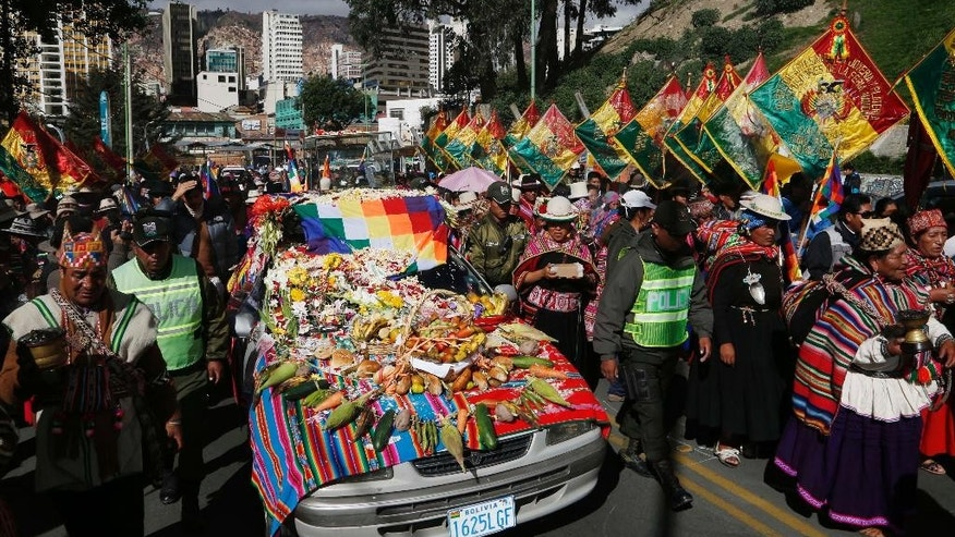 "Hundreds accompany the Bolivian deity statuette ""illa of Ekeko"" as it is driven to the Alasitas Fair, in which Ekeko is the central figure, in La Paz, Bolivia, Saturday, Jan. 24, 2015. The pre-Columbian figurine that symbolizes abundance was recently returned to Bolivia by the National Museum of Berna in Switzerland, 156 years after being taken away from its native country. ""Alasitas"" is an Aymaran word that means ""buy me,"" and is the name of the annual fair where people buy miniature items that represent things they hope to attain within the year. (AP Photo/Juan Karita) (AP Photo/Juan Karita)"