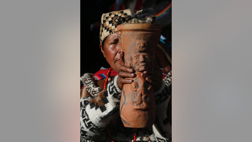 "An Andean religious leader holds an urn with burning incense in a procession of the Bolivian deity statuette ""illa of Ekeko"" as it is driven to the Alasitas Fair, in which Ekeko is the central figure, in La Paz, Bolivia, Saturday, Jan. 24, 2015. The pre-Columbian figurine that symbolizes abundance was recently returned to Bolivia by the National Museum of Berna in Switzerland, 156 years after being taken away from its native country. ""Alasitas"" is an Aymaran word that means ""buy me,"" and is the name of the annual fair where people buy miniature items that represent things they hope to attain within the year. (AP Photo/Juan Karita)(AP Photo/Juan Karita)"