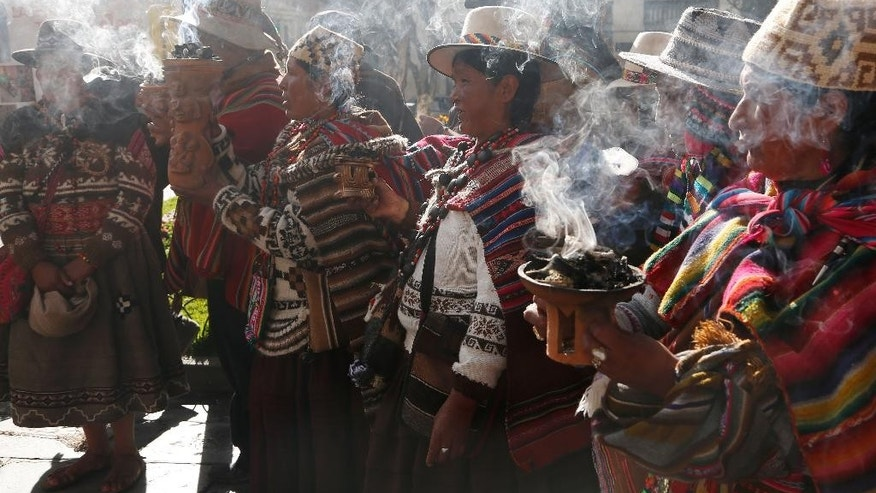 "Andean religious leaders carry urns with burning incense in a procession of the Bolivian deity statuette ""illa of Ekeko"" as it is driven to the Alasitas Fair, in which Ekeko is the central figure, in La Paz, Bolivia, Saturday, Jan. 24, 2015. The pre-Columbian figurine that symbolizes abundance was recently returned to Bolivia by the National Museum of Berna in Switzerland, 156 years after being taken away from its native country. ""Alasitas"" is an Aymaran word that means ""buy me,"" and is the name of the annual fair where people buy miniature items that represent things they hope to attain within the year. (AP Photo/Juan Karita)"