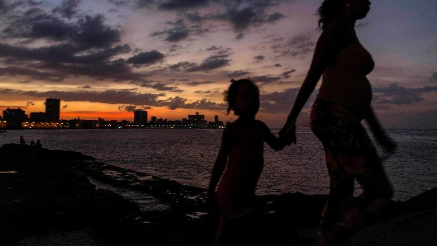 FILE - In this Jan. 3, 2015, file photo, a woman leads a girl by the hand to the Malecon as the sun sets in Havana, Cuba. Everyone warns you Old Havana is a facade, but it's impossible not to be taken by its charms. For a foreigner who isn't coming with predetermined notions of Cuba as global boogeyman or socialist paradise, each alley and avenue, each conversation with a Cuban, complicates the picture.  (AP Photo/Ramon Espinosa)