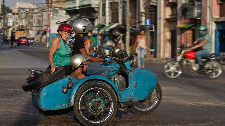 FILE - In this Oct. 8, 2014, file photo, people ride in an Ural Soviet motorcycle in Havana, Cuba. Everyone warns you Old Havana is a facade, but it's impossible not to be taken by its charms. For a foreigner who isn't coming with predetermined notions of Cuba as global boogeyman or socialist paradise, each alley and avenue, each conversation with a Cuban, complicates the picture.  (AP Photo/Franklin Reyes, File)