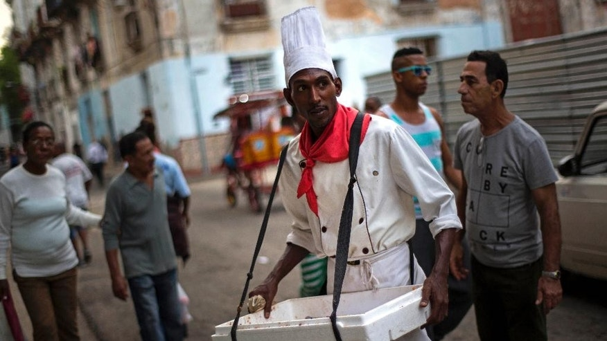 FILE - In this Jan. 17, 2015, photo, Yurien Rojas, who sells custard filled pastries known as Señoritas, waits for customers on a street in Havana, Cuba. Everyone warns you Old Havana is a facade, but it's impossible not to be taken by its charms. For a foreigner who isn't coming with predetermined notions of Cuba as global boogeyman or socialist paradise, each alley and avenue, each conversation with a Cuban, complicates the picture. . (AP Photo/Ramon Espinosa, File)