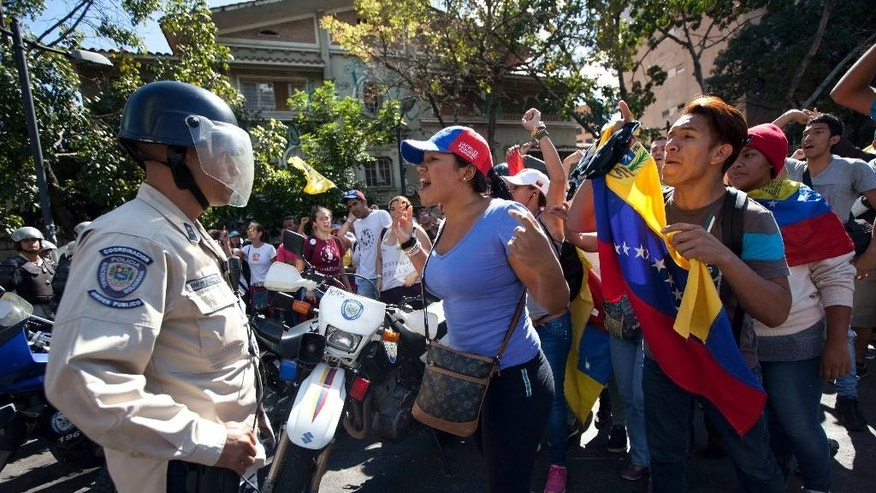 People chant anti-government slogans as police block marchers' access to downtown, in an event billed as the ¨March of the empty pots¨, in Caracas, Venezuela, Saturday, Jan. 24, 2015. Thousands of opponents of President Nicolas Maduro marched in the capital Saturday to denounce the socialist government for a deepening economic crisis marked by widespread shortages and galloping inflation. (AP Photo/Ariana Cubillos)