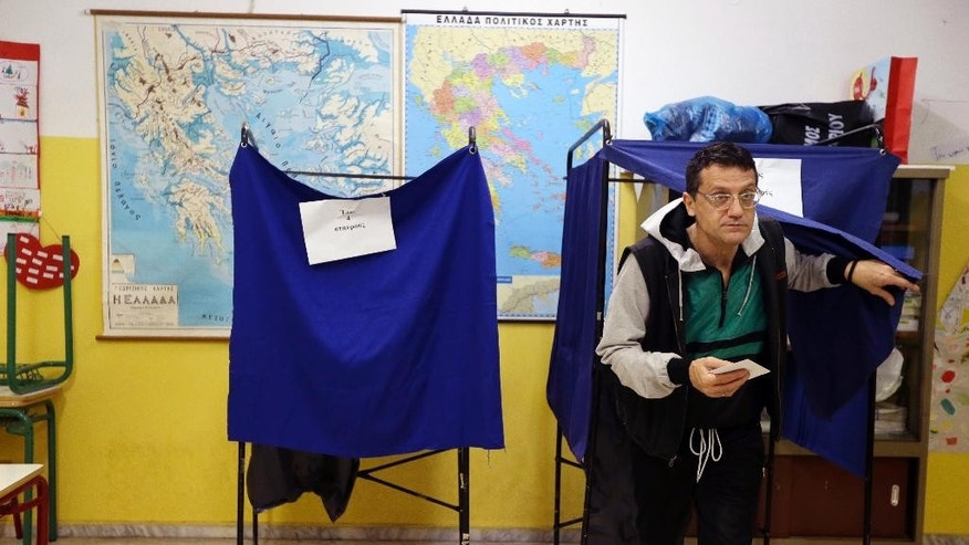 A man casts his vote at a polling station in Athens Sunday, Jan. 25, 2015. Greeks were voting Sunday in an early general election crucial for the country's financial future, with the radical left Syriza party of Alexis Tsipras tipped as the favorite to win, although possibly without a large enough majority to form a government. (AP Photo/Thanassis Stavrakis)