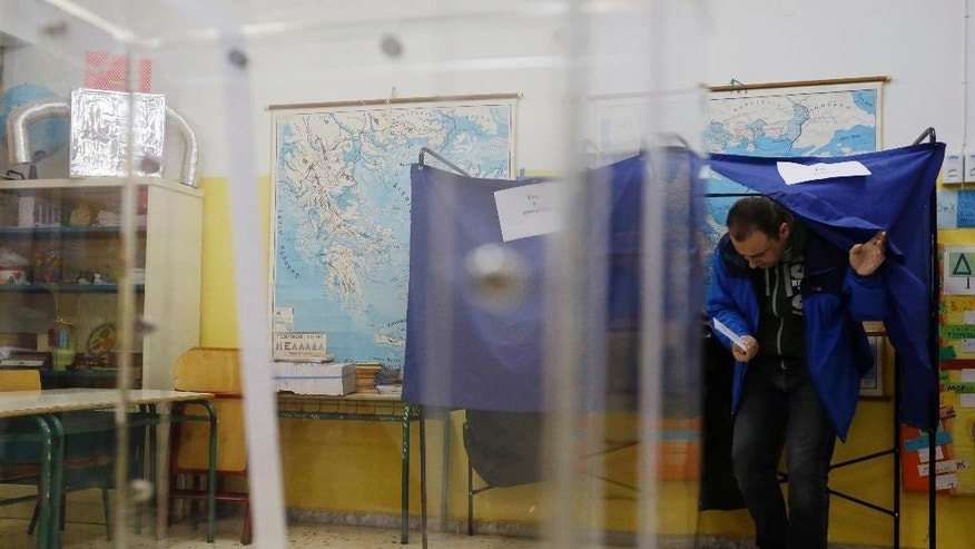 A man casts his vote at a polling station in Athens, Sunday, Jan. 25, 2015. Greeks were voting Sunday in an early general election crucial for the country's financial future, with the radical left Syriza party of Alexis Tsipras tipped as the favorite to win, although possibly without a large enough majority to form a government. (AP Photo/Thanassis Stavrakis)