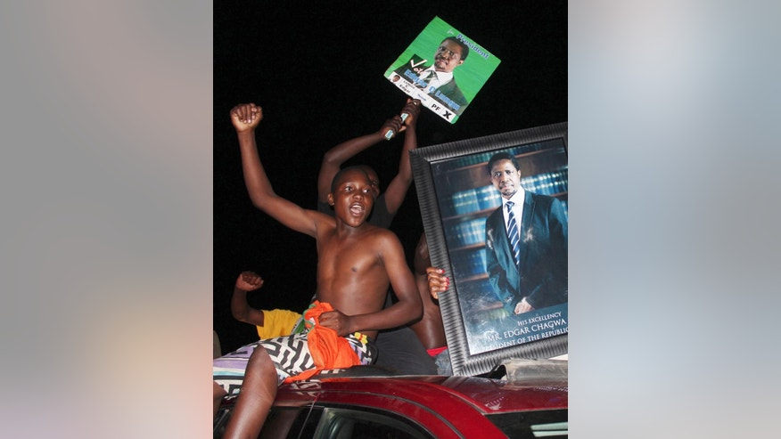 Supporters of the Patriotic Front hold portraits of their presidential candidate Edgar Lungu and celebrate after an announcement that Lungu won the presidential elections in Lusaka, Zambia, Saturday, Jan. 24, 2015. Lungu narrowly defeated his rival Hakainde Hichilema in the contest to succeed Michael Sata, who died in office in October at 77. (AP Photo/Moses Mwape)
