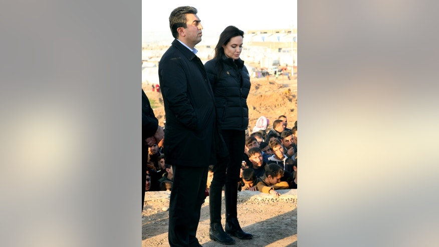 Special Envoy of the United Nations High Commissioner for Refugees (UNHCR), Angelina Jolie stands with Dohuk governor, Farhad Atrushi, at Khanke camp in Dahuk, north of the Kurdistan region, 260 miles (430 kilometers) northwest of Baghdad, Iraq, Sunday, Jan. 25, 2015. Actress and United Nations envoy Angelina Jolie called on the international community to do more for people in Iraq and Syria, during a visit to a refugee camp in northern Iraq on Sunday. (AP Photo/Seivan M. Selim)