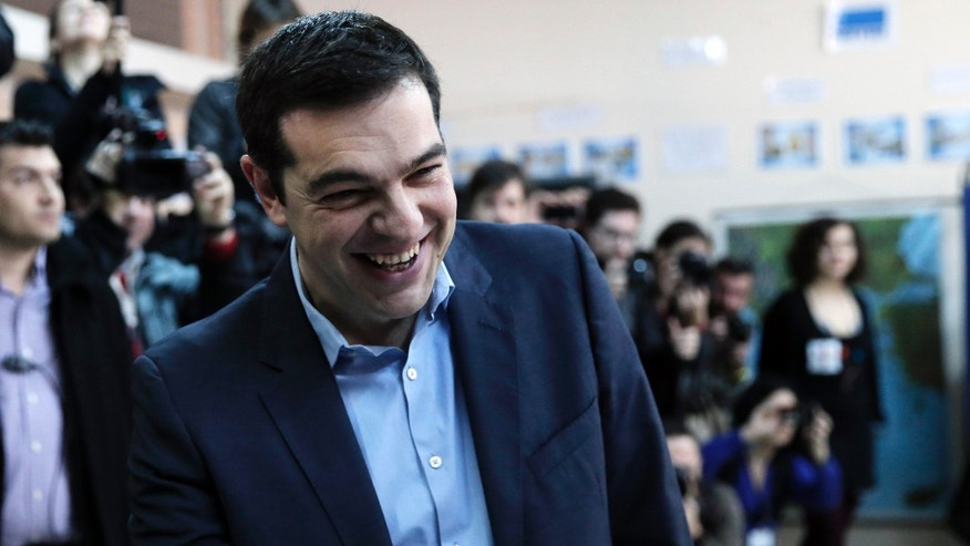Jan. 25, 2015: Alexis Tsipras, leader of Greece's Syriza left-wing main opposition party laughs as he arrives to cast his vote at a polling station in Athens.