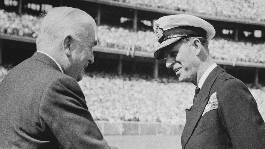 FILE - In this Nov. 21, 1956 file photo, Britain's Prince Philip, right, is welcomed to Olympic Stadium in Melbourne, Australia by Australian Prime Minister Robert Menzies as the Duke of Edinburgh officially opens the Olympic games. Australia's prime minister on Monday, Jan. 26, 2015 dismissed criticism of his decision to make the husband of Queen Elizabeth II an Australian knight, saying Philip has a long history of service Down Under. Prime Minister Tony Abbott's announcement that the duke would be awarded Australia's highest honor came on Australia's national holiday, prompting some to question the wisdom of knighting a British royal on a day meant to commemorate Australians. (AP Photo/File)