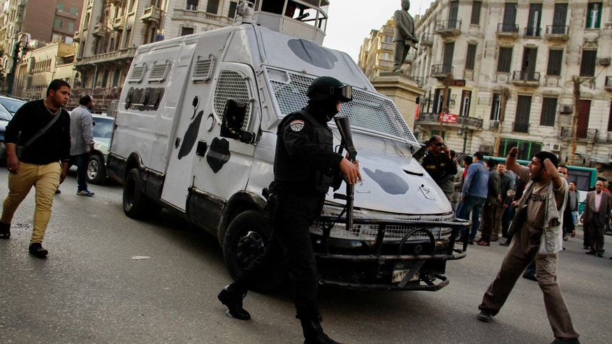 Jan. 22, 2015: A member of the Egyptian security forces disperses people gathering to protest against a court order to release the two sons of ousted Egyptian President Hosni Mubarak in Talaat Harb Square downtown Cairo, Egypt. (AP)