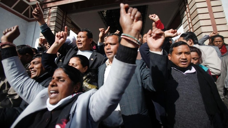 Nepalese opposition lawmakers shout slogans as they walk out of the Constituent Assembly in Kathmandu, Nepal, Sunday, Jan. 25, 2015. Nepal's ruling coalition on Sunday took a step toward drafting a new constitution, angering the opposition and pushing the Himalayan country further into political turmoil. (AP Photo/Niranjan Shrestha)