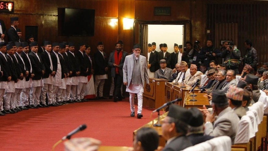 Nepalese Prime Minister Sushil Koirala, center, arrives to attend a meeting of the Constituent Assembly in Kathmandu, Nepal, Sunday, Jan. 25, 2015. Nepal's ruling coalition on Sunday took a step toward drafting a new constitution, angering the opposition and pushing the Himalayan country further into political turmoil. (AP Photo/Niranjan Shrestha)
