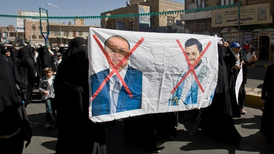 Protesters hold a poster depicting Yemen's President Abed Rabbo Mansour Hadi, left, and Abdul-Malik al-Houthi, a leader of Shiite rebels who hold the capital, Sanna, amid a power vacuum, during a demonstration in Sanaa on Saturday, Jan. 24, 2015. Some 20,000 marched Saturday across the capital, where demonstrators converged on the house of Hadi, who resigned Thursday along with his Cabinet. (AP Photo/Hani Mohammed)
