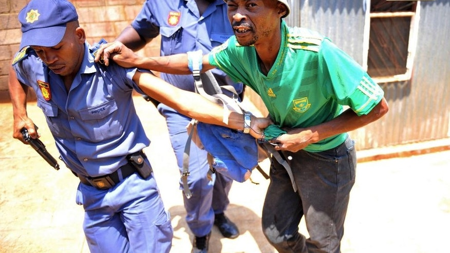 In this photo taken Thursday, Jan 22, 2015 police arrest a man suspected of looting a store in Soweto, South Africa. South African authorities have re-established order _ for now _ in Soweto and other Johannesburg townships, after a week of looting of foreign-owned shops and violence in which four people were killed. (AP Photo)