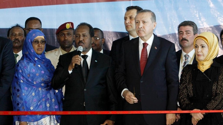 Turkey's President Recep Tayyip Erdogan, center, and Somalia President Hassan Sheikh Mohamud, second left, with their wives, attend the cutting of the tape for the new airport terminal in the capital Mogadishu, Sunday Jan. 25, 2015. Under tight security Turkish President, Recep Tayyip Erdogan, launched development projects sponsored by his government including an airport terminal in the Somali capital, Mogadishu. (AP Photo/Farah Abdi Warsameh)