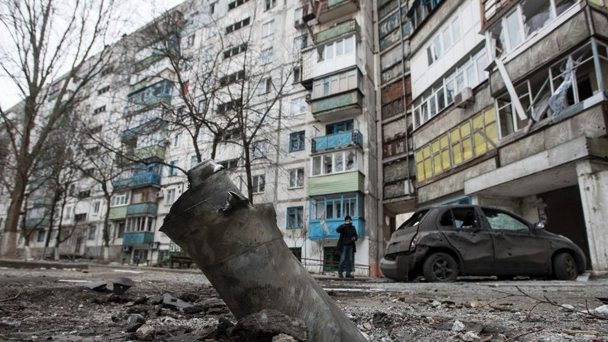 A piece of an exploded Grad missile is photographed outside an apartment building in Vostochniy, district of Mariupol, Eastern Ukraine, Sunday, Jan. 25, 2015. Indiscriminate rocket fire slammed into a market, schools, homes and shops Saturday in Ukraine's southeastern city of Mariupol, killing at least 30 people, authorities said. The Ukrainian president called the blitz a terrorist attack and NATO and the U.S. demanded that Russia stop supporting the rebels. (AP Photo/Evgeniy Maloletka)