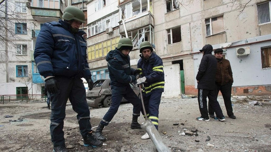 Rescue workers try to pull out a piece of an exploded Grad missile outside an apartment building in Vostochniy district of Mariupol, Eastern Ukraine, Sunday, Jan. 25, 2015. Indiscriminate rocket fire slammed into a market, schools, homes and shops Saturday in Ukraine's southeastern city of Mariupol, killing at least 30 people, authorities said. The Ukrainian president called the blitz a terrorist attack and NATO and the U.S. demanded that Russia stop supporting the rebels. (AP Photo/Evgeniy Maloletka)