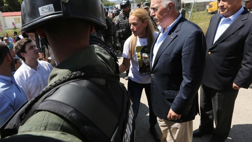 Colombia's former President Andres Pastrana, second from right, stands with Lilian Tintori, wife of jailed opposition leader Leopoldo Lopez, center, and Chile's former President Sebastian Pinera, far right, as they're blocked by National Guard from entering Ramo Verde prison where Lopez is jailed in Los Teques, on the outskirts of Caracas, Venezuela, Sunday, Jan. 25, 2015. The group tried to visit Lopez but were denied access. The opposition leader was jailed in February 2014, accused of inciting violent protests in early 2014, and has a threat of a 13-year prison term hanging over him. (AP Photo/Ariana Cubillos)