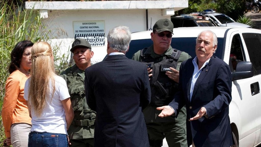 Colombia's former President Andres Pastrana, right, Chile's former President Sebastian Pinera, center, back to camera, Lilian Tintori, wife of jailed opposition leader Leopoldo Lopez, left, back to camera, and Lopez's mother Antonieta Mendoza de Lopez, far left, speak with National Guard officers outside Ramo Verde prison where Lopez is jailed in Los Teques, on the outskirts of Caracas, Venezuela, Sunday, Jan. 25, 2015. The group tried to visit Lopez but were denied access. Lopez was jailed in February 2014, accused of inciting violent protests, and has a threat of a 13-year prison term hanging over him. (AP Photo/Ariana Cubillos)