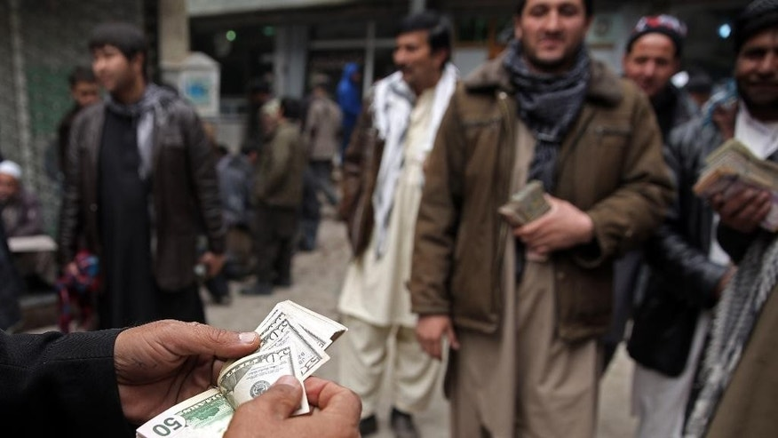 FILE - In this Monday, Jan. 12, 2015 file photo, An Afghan money changer, left, counts a pile of currency at the Money and Exchange Market in Kabul. Afghanistan's currency, the Afghani, stands at 57.60 against the U.S. dollar. Afghanistan's fragile economy has lost around a third of its value in the past year as the international military and aid organizations that poured in cash for more than a decade have drastically scaled back after U.S. President Barack Obama declared an end to the 13-year war against the Taliban _ leaving the government struggling for funds and key sectors lacking investment, economists, analysts and officials said. (AP Photo/Massoud Hossaini, File)