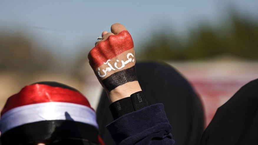 """A woman raises her fist painted with Yemen's flag and Arabic writing that reads, """"Yemen is safe,"""" to protest against the Houthi Shiite rebels who hold the capital, Sanna, during a demonstration in Sanaa on Saturday, Jan. 24, 2015. Some 20,000 marched Saturday across the capital, where demonstrators converged on the house of President Abed Rabbo Mansour Hadi, who resigned Thursday along with his Cabinet. (AP Photo/Hani Mohammed)"""