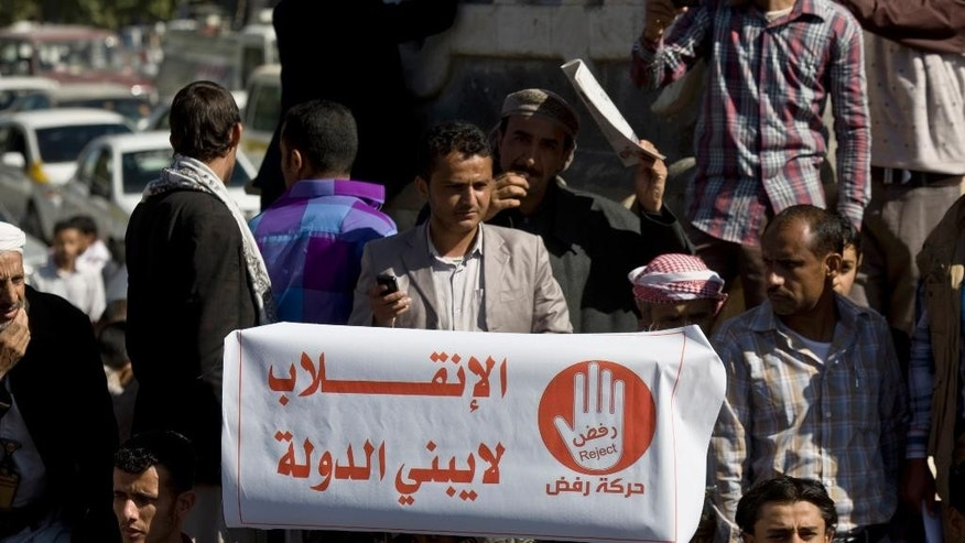 """A protester holds a banner with Arabic writing that reads, """"The coup does not build a country,"""" protesting against Houthi Shiite rebels who hold the capital, Sanna, amid a power vacuum as they hold a demonstration in Sanaa on Saturday, Jan. 24, 2015. Some 20,000 marched Saturday across the capital, where demonstrators converged on the house of President Abed Rabbo Mansour Hadi, who resigned Thursday along with his Cabinet. (AP Photo/Hani Mohammed)"""