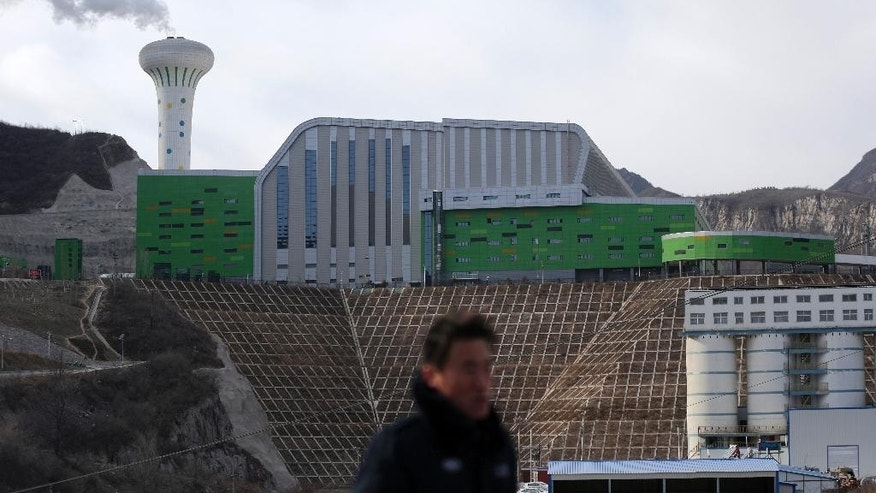 In this Dec. 16, 2014 photo, a security guard walks past the Lujiashan incinerator in the Mentougou districts of Beijing, China. A greater willingness by Chinese authorities to listen to public concerns on issues such as the environment appears to be an attempt to keep unhappiness in check and maintain the Communist Party's grip on power even as it continues to squash political dissent and censor the media. (AP Photo/Andy Wong)