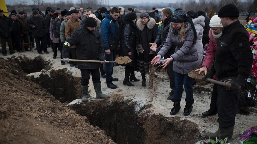 ALTERNATIVE CROP OF MOSB114 - Relatives of Alexander Demyanenko, victim of Saturday shelling pour soil at his grave during funerals in Mariupol, Ukraine, on Monday Jan. 26, 2015. At least 5,100 people have been killed in eastern Ukraine since fighting began in April 2014, but violence this week was the most intense since a cease-fire deal was signed in September. Mariupol, a strategic port city on the Black Sea still controlled by Ukrainian forces, has been a symbolic bulwark against the separatist advance that if captured by the rebels would give them a land corridor to Russia-controlled Crimea. The city had been relatively quiet for months before Saturday's attack.(AP Photo/Evgeniy Maloletka)