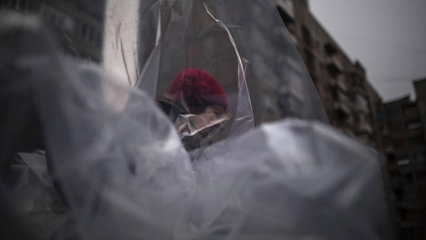 A woman carries plastic to cover broken windows after Saturday's shelling at Vostochniy district of Mariupol, Ukraine, Monday, Jan. 26, 2015. At least 5,100 people have been killed in eastern Ukraine since fighting began in April 2014, but violence this week was the most intense since a cease-fire deal was signed in September. (AP Photo/Evgeniy Maloletka)